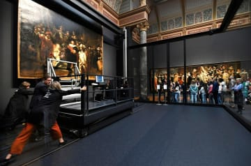 レンブラントの「夜警」の修復準備作業を、ガラス越しに見守る美術館の来訪者ら=8日、アムステルダム(ロイター=共同)