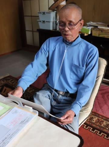 自宅で年金の書類を確認する福田さん=諫早市