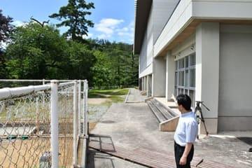 クマが目撃された現場付近。体育館(右)の裏の山方向に逃げ去ったという=白鷹町・鮎貝小