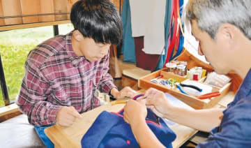 縫製スタッフに上着を修繕してもらう会沢さん(左)