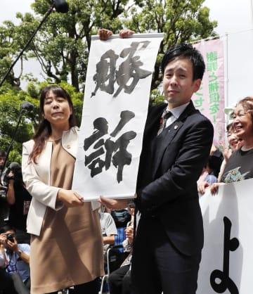 ハンセン病家族訴訟で熊本地裁が国に賠償を命じ、勝訴の垂れ幕を掲げる原告側弁護士=6月28日、熊本地裁前
