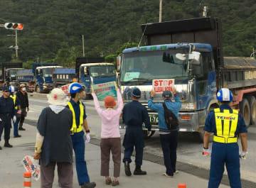 名護市辺野古の新基地建設の埋め立て土砂を積む車両に抗議する市民ら=9日午前10時10分ごろ、名護市安和