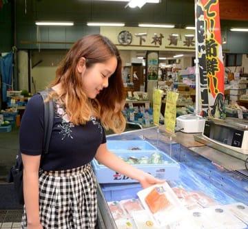 鮮魚店でサケを手に取る女子大生。サケ・サーモンの人気が断トツという=5日、熊本市中央区の子飼商店街