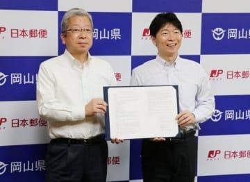 協定書に署名した横山社長(左)と伊原木知事
