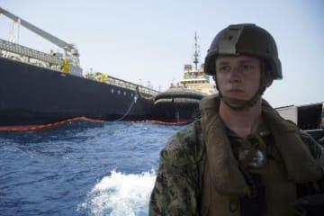 イラン沖で攻撃を受けた日本の海運会社が運航するタンカーと、米海軍兵=6月19日、アラブ首長国連邦(UAE)フジャイラ沖(AP=共同)