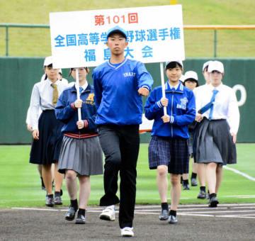 引き締まった表情で行進する山川選手(中央)