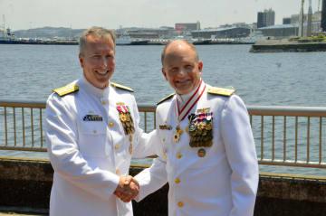 在日米海軍新司令官のブライアン・フォート少将(左)と握手する前任のグレゴリー・フェントン少将=10日、神奈川県横須賀市