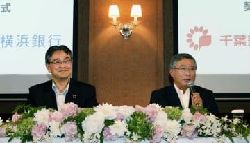 記者会見で笑顔を見せる横浜銀行の大矢恭好頭取(左)と千葉銀行の佐久間英利頭取=10日午後、東京都中央区