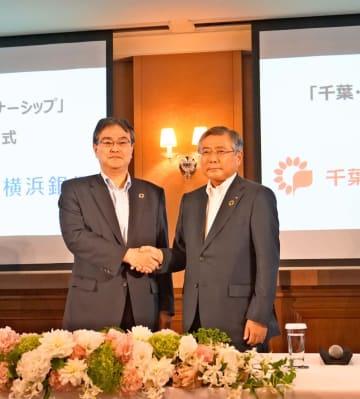握手する横浜銀行の大矢恭好頭取(左)と千葉銀行の佐久間英利頭取(右)=東京都中央区