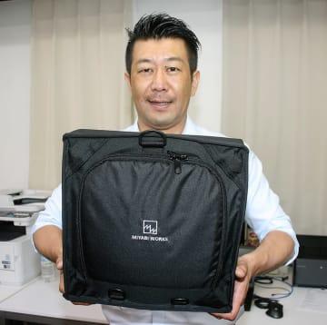 防災バッグ「OTE」を持つ林社長