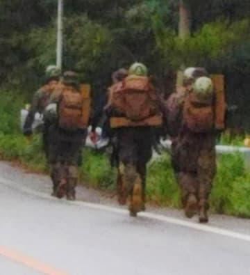 米軍北部訓練場「N1」地区出入り口前を行軍する武装米兵=10日、東村高江(「ヘリパッドいらない住民の会」提供)