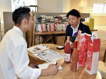 主要観光地の道後商店街に出店する業者に、地元産品を売り込む宇和島市の事業者(右)=10日午前、松山市道後湯之町