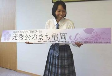 明智光秀をイメージした看板のデザインを持つ和多田さん(亀岡市役所)