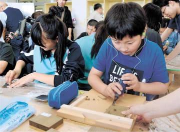 電動彫刻刀で埋もれ木にしま模様を入れる児童=仙台市宮城野区の岡田小