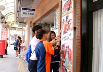 商店街にポスターを張るアルビレックス新潟レディースの選手=9日、新発田市