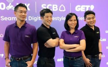 ゴジェックへの出資と業務提携を発表した、サイアム商業銀行のアピパン共同頭取(右から2人目)と、ゴジェックの国際事業部門トップのアンドリュー・リー氏(同3人目)ら=11日、バンコク(NNA撮影)