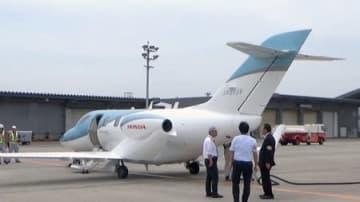 新潟空港に到着したホンダジェットを前に話し合う新潟市の担当者ら=新潟市東区