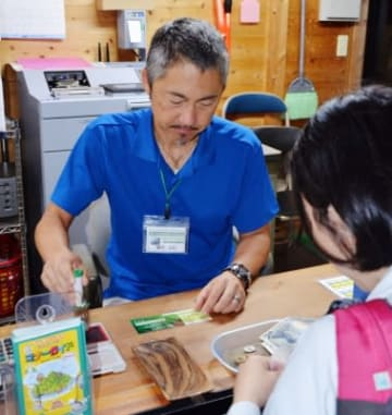 協力金付きの登山バスチケットを販売する協議会職員=屋久島町安房