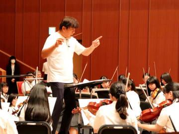 迫力ある動きで母校の生徒たちの演奏を指揮する佐渡さん(京都市中京区・京都堀川音楽高校)
