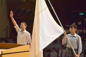 結団式で選手宣誓をする瀬田工高の谷口さんと団旗を持つ林沼さん(大津市島の関・市民会館)