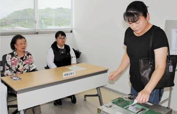 期日前投票所で投票立会人を務める高校3年の千田さん(中央)
