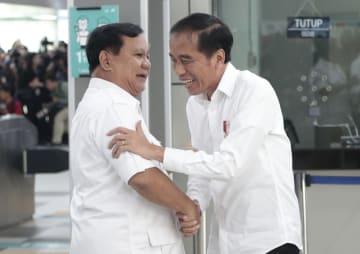 インドネシア・ジャカルタで、ジョコ大統領(右)と握手する野党党首プラボウォ氏=13日(AP=共同)