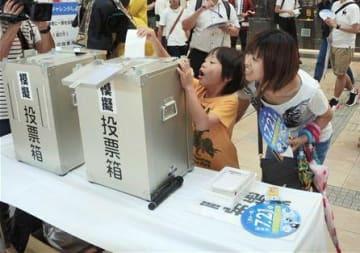 県選挙管理委員会の街頭啓発活動で模擬投票を体験する人たち=13日、熊本市