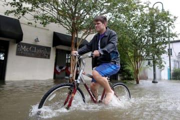 冠水した道路で自転車に乗る人=13日、米南部ルイジアナ州沿岸部(ロイター=共同)