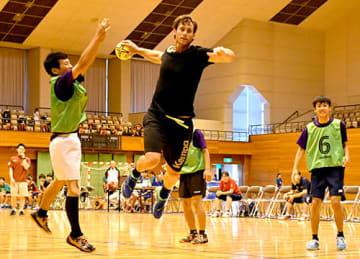 世界レベルの技を披露するハンドボールドイツ代表のウーベ・ゲンスハイマー主将(中央)=東根市民体育館