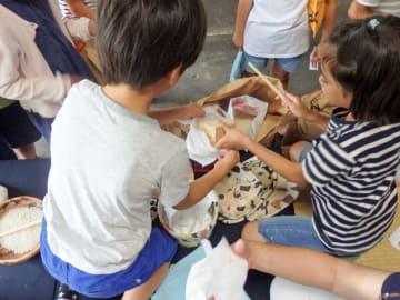 一合升で販売する米を量る児童=藤沢市内