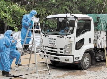 汚染廃棄物を積んだトラック周辺の空間線量を図る作業員=6月、宮城県大崎市古川(写真の一部を加工しています)