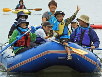 ラフティングボートに乗ってパドルを漕ぎ水の感触を楽しむ参加者