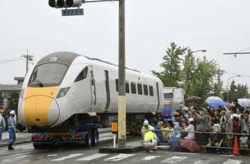 トレーラーに載せられて道路上を輸送される高速鉄道車両=14日、山口県下松市