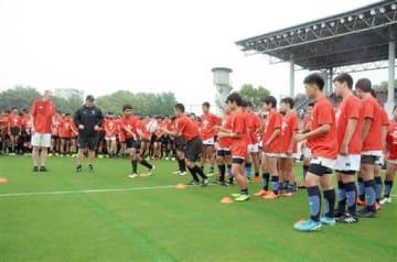 ウェールズラグビー協会のスタッフらからパスを教わる中学生=熊本市