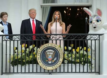 WASHINGTON, DC - APRIL 17: U.S. President Donald Trump (C) delivers remarks from the Truman Balcony with first lady Melania Trump and their son Barron Trump (L) during the 139th Easter Egg Roll on the South Lawn of the White House April 17,...