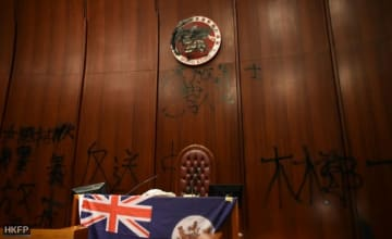 Protesters defaced the emblem of Hong Kong, spray-painted slogans, and unfurled the colonial-era flag. Photo: Thammakhun John Crowcroft/HKFP.