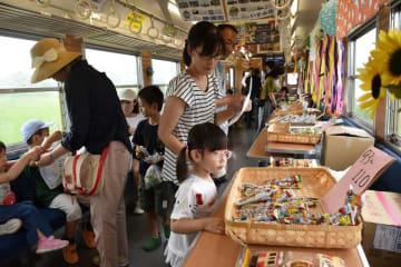 好みの駄菓子を選ぶ乗客=いすみ鉄道