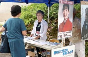 署名を呼び掛ける中村クニさんや支援者=14日、長岡市の山古志闘牛場