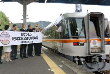 名古屋駅に向けて出発する特急「紀勢本線全通60周年号」を見送る関係者=15日午後、JR熊野市駅