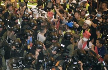 警官隊(手前)やデモ隊らで騒然とするショッピングモール内=14日、香港・新界地区(共同)