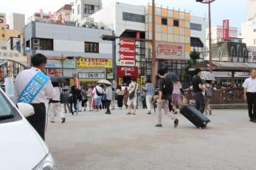 長崎市中心部で街頭演説する吉田氏(左)=鉄橋