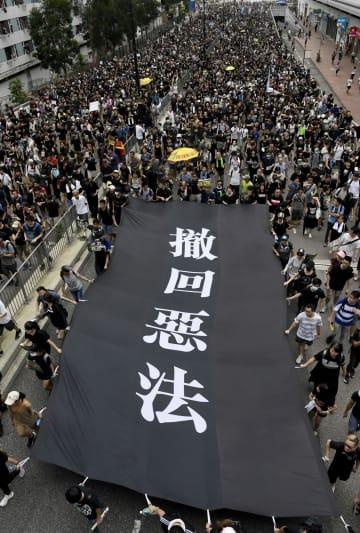 「逃亡犯条例」改正案の完全撤回などを求め、香港・新界地区でデモ行進する人たち=14日(共同)