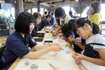 大学生に教わりながらアクセサリー作りに励む子どもたち=人吉市