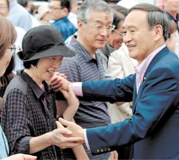 秋田入りして有権者らと握手を交わす菅官房長官=14日、湯沢市