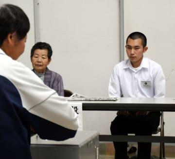 期日前投票所で立会人を務める大崎耀大さん(右)