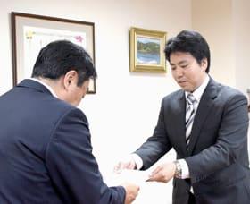 小笠原市長に答申書を手渡す田瀨会長(右)