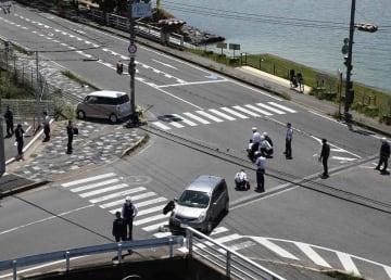 2台の事故車両の周囲で現場検証する署員ら。園児らは左奥の歩道で信号待ちをしていた(5月8日、大津市大萱6丁目