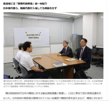 韓国メディアが「倉庫会議」と報じた日韓実務者会議。韓国側代表(右)の後方に山積みされたパイプ椅子が見える(ハンギョレ日本語版オンライン12日付紙面より)