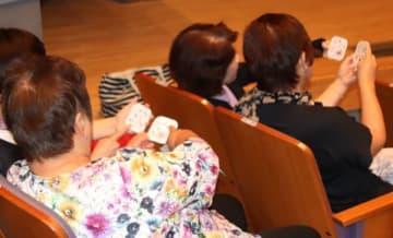 【反射神経活性化カードを体験する参加者ら=松阪市嬉野権現前町の嬉野ふるさと会館で】