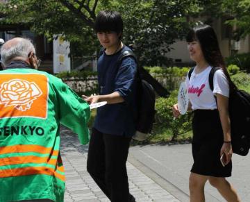 参院選の投票を呼び掛けるうちわを受け取る学生(宇治市槙島町、京都文教大・短期大)